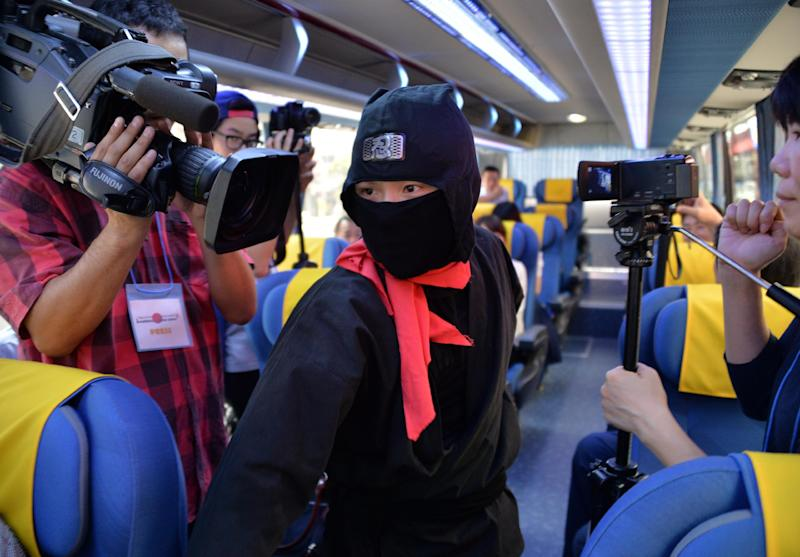 A member of pantomime group Gabez clad as a ninja performs in a sightseeing bus in Tokyo on July 16, 2014
