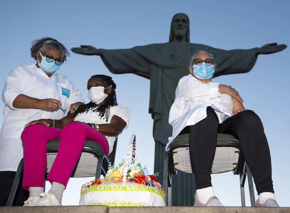RIO DE JANEIRO, BRAZIL - JANUARY 18: (L-R) Adelia Maria dos Santos, 71, a Municipal Health Secretariat worker since 1979 administers a dose of the CoronaVac vaccine to Terezinha da Conceicao, 80, and Dulcinea da Silva Lopes, 59 at the feet of the statue of Christ the Redeemer on January 18, 2021 in Rio de Janeiro, Brazil. Dulcinea is a nursing technician at Hospital Municipal Ronaldo Gazolla and has been working on the front lines of the fight against Covid-19 for 8 months. Terezinha has lived in a shelter managed by the city since 2015, when her house was demolished by the Civil Defense where she lived in a situation of vulnerability and social risk. The state of Rio de Janeiro will immunize with the first vaccine shipment Health workers, institutionalized people aged 60 or over, Indigenous and quilombolas on their own land and institutionalized people with disabilities. The CoronaVac vaccine was developed by the Chinese laboratory Sinovac in partnership with the Butantan Institute. (Photo by Buda Mendes/Getty Images)