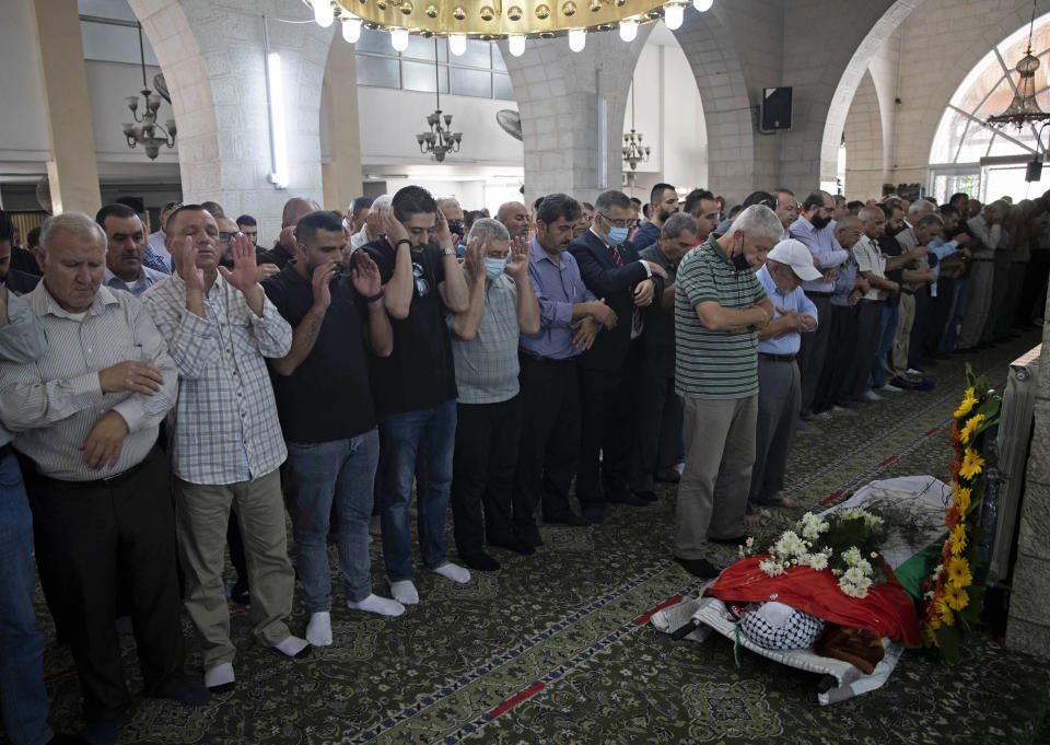 Palestinian mourners pray near the body of Suha Jarrar, 30-year-old, daughter of Khalida Jarrar who is a prisoner in an Israeli jail, during her funeral, in the West Bank city of Ramallah, Tuesday, July 13, 2021. Khalida Jarrar, 58, a leading member of the Popular Front for the Liberation of Palestine, has been in and out of Israeli prison in recent years. Palestinian activists and human rights groups urged Israel to allow Jarrar to attend her daughter's funeral. (AP Photo/Majdi Mohammed)