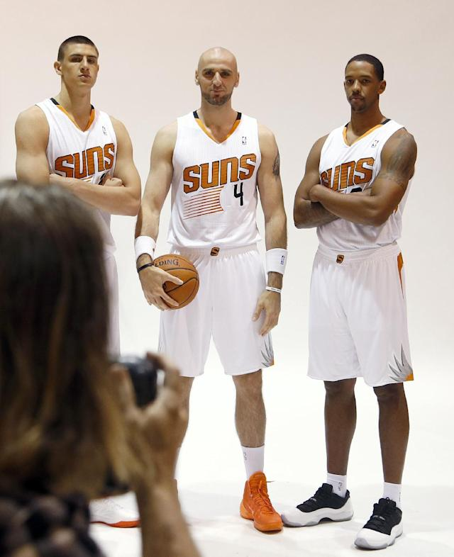 Phoenix Suns' Channing Frye, right, poses with teammates Marcin Gortat (4), of Poland, and rookie center Alex Len for team photographer Barry Gossage during the team's NBA basketball media day on Monday, Sept. 30, 2013, in Phoenix. The Suns announced that Frye has been cleared to join the team's training camp, a year after it was found that Frye would have to miss the entire basketball season because of an enlarged heart. (AP Photo/Ross D. Franklin)