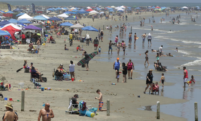 FILE - In this May 23, 2020 file photo, people gather on the beach in Port Aransas, Texas. Beachgoers are being urged to practice social distancing to guard against COVID-19. (AP Photo/Eric Gay, File)