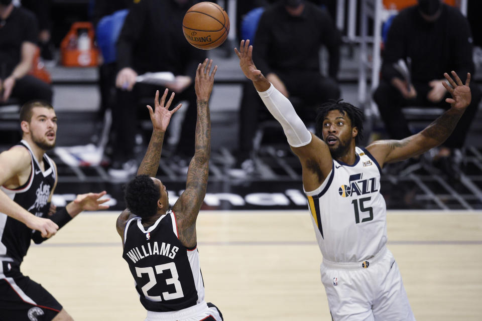 Los Angeles Clippers guard Lou Williams (23) shoots while Utah Jazz center Derrick Favors defends during the first half of an NBA basketball game in Los Angeles, Friday, Feb. 19, 2021. (AP Photo/Kelvin Kuo)