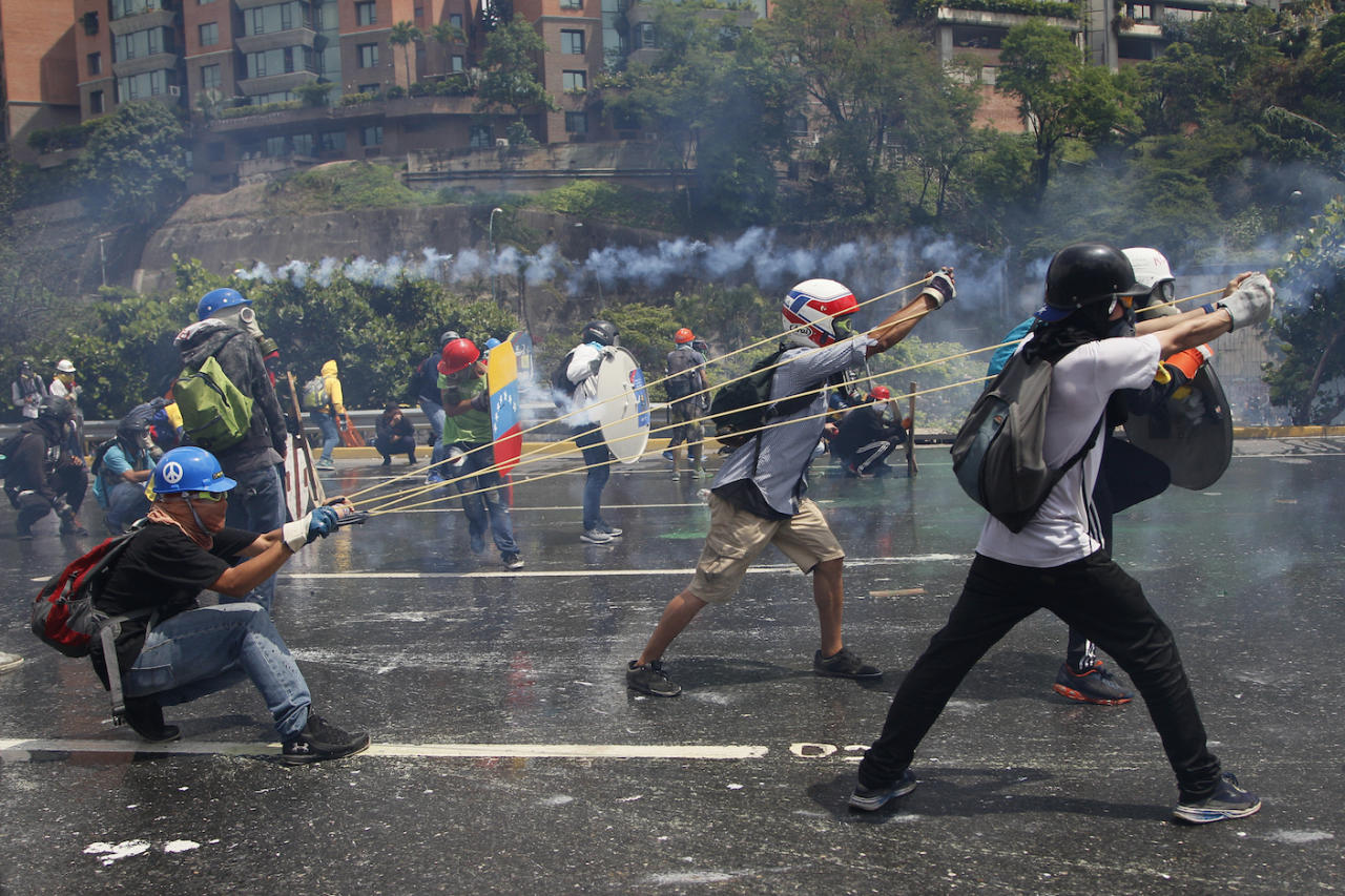 <p>Anti-government protesters aim a slingshot holding a glass bottle of faeces during clashes with security forces blocking an opposition march attempting to reach the Supreme Court in Caracas, Venezuela (AP Photo/Ariana Cubillos) </p>