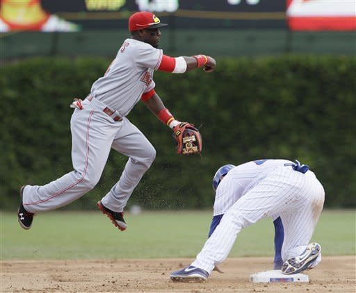 Cincinnati Reds second baseman Brandon Phillips, left, throws to first after forcing out Chicago Cubs' Anthony Rizzo during the first inning of a baseball game in Chicago, Friday, Aug. 10, 2012. Alfonso Soriano was safe at first. (AP Photo/Nam Y. Huh)