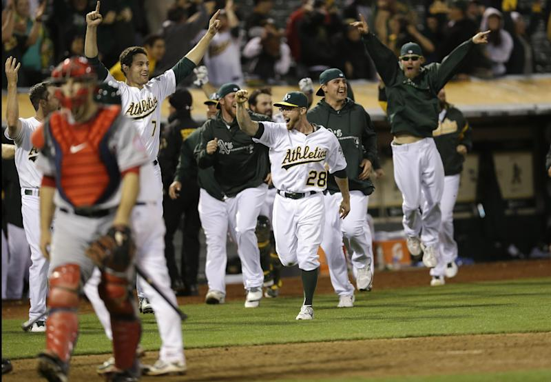 The Oakland Athletics celebrate a game- winning two-run home run by Brandon Moss during the nineteenth inning of a baseball game against the Los Angeles Angels on Tuesday, April 30, 2013 in Oakland. Calif. Oakland won 10-8 in 19 innings. (AP Photo/Marcio Jose Sanchez)