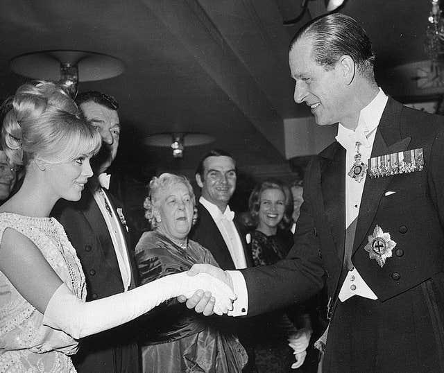 The Duke of Edinburgh shakes hands with Swedish actress Britt Ekland at the Royal Film Performance in London