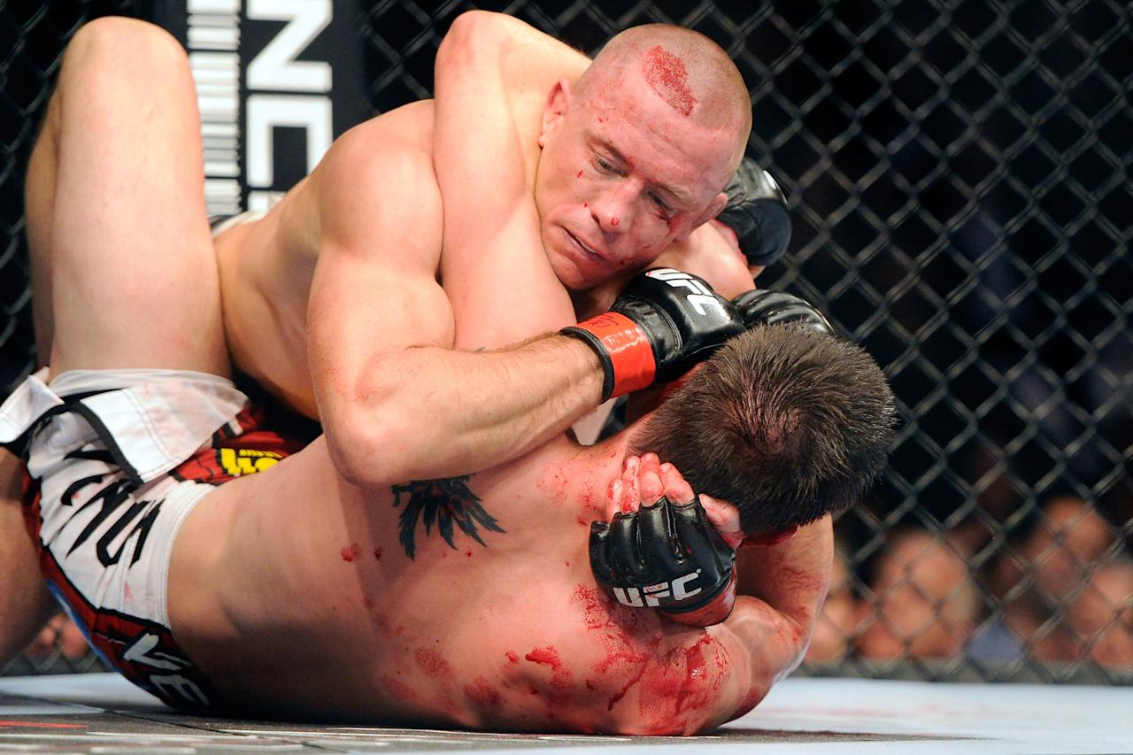 Nov 17, 2012; Montreal, QC, Canada;  Georges St-Pierre (top) holds on to Carlos Condit (bottom) during second round action of their Welterweight Championship bout at UFC 154 at the Bell Centre.  Mandatory Credit: Eric Bolte-US PRESSWIRE
