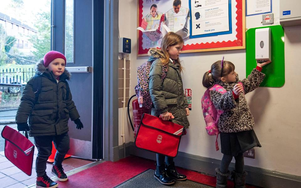 Pupils sanitise their hands as they arrive at Inverkip Primary School - Jane Barlow /PA