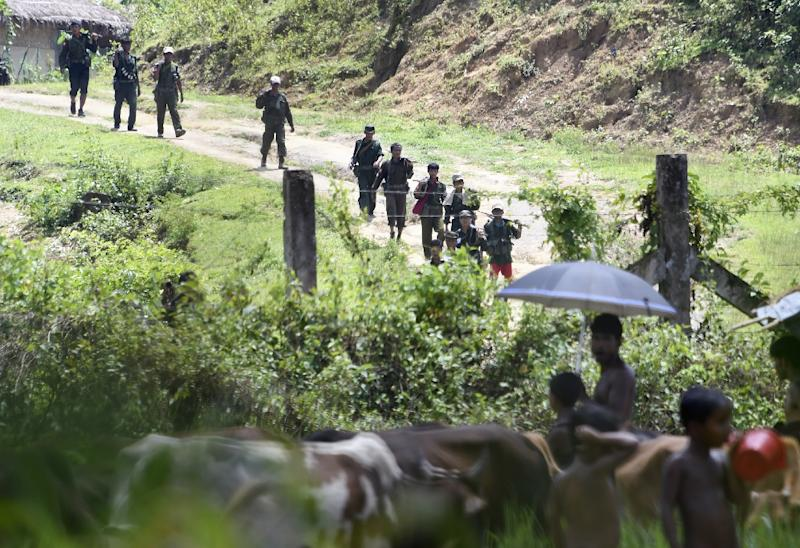 Rohingya Muslim refugees in Jalpatoli refugee camp, in the no-man's land between Myanmar and Bangladesh, watch as Myanmar soldiers patrol on the other side of the border, near Gumdhum village in Ukhia on September 16, 2017 (AFP Photo/Dominique FAGET)