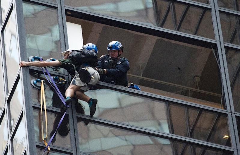 New York police officers grab a young man some three hours after he started his ascent of Trump Tower using five suction cups (AFP Photo/Bryan R. Smith)