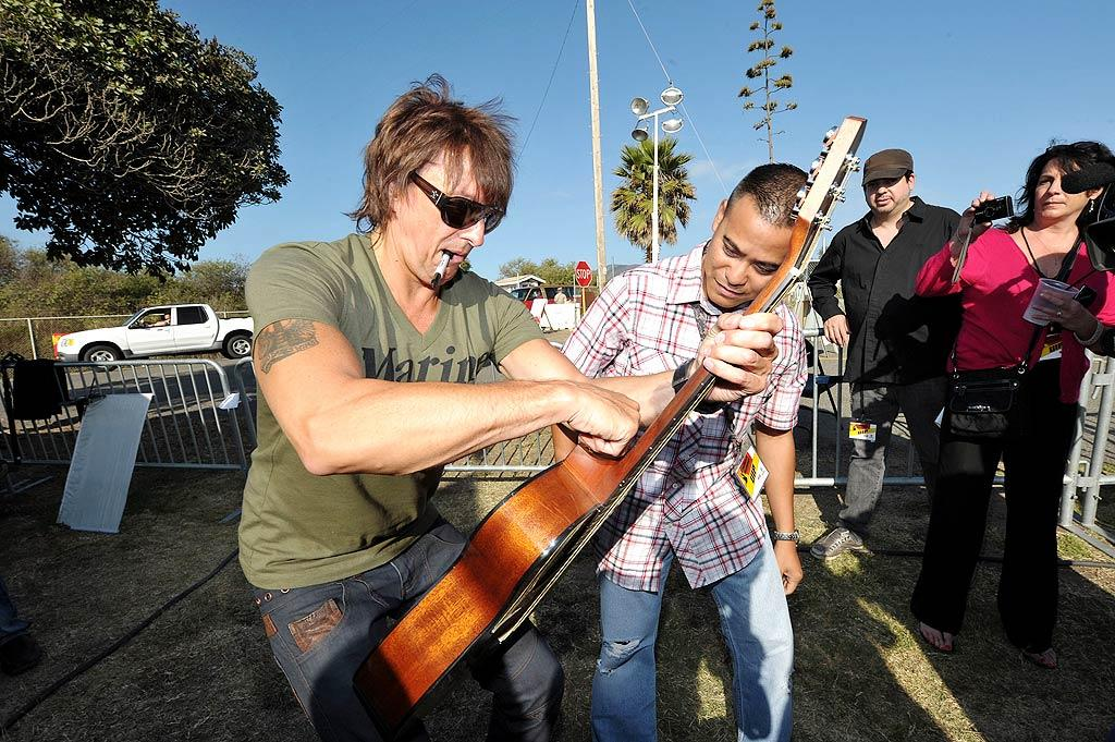 "Richie Sambora showed his support for the troops last weekend when he paid a visit the Marine base Camp Pendleton in Oceanside, California, to hand out autographed guitars to a few lucky Marines who won a contest. The full-size guitars fold in half and fit in a specially made backpack so that they can be taken anywhere the troops go. Sambora also played a few classic Bon Jovi tunes for the military members. John Shearer/<a href=""http://www.gettyimages.com/"" target=""new"">GettyImages.com</a> - August 19, 2011"