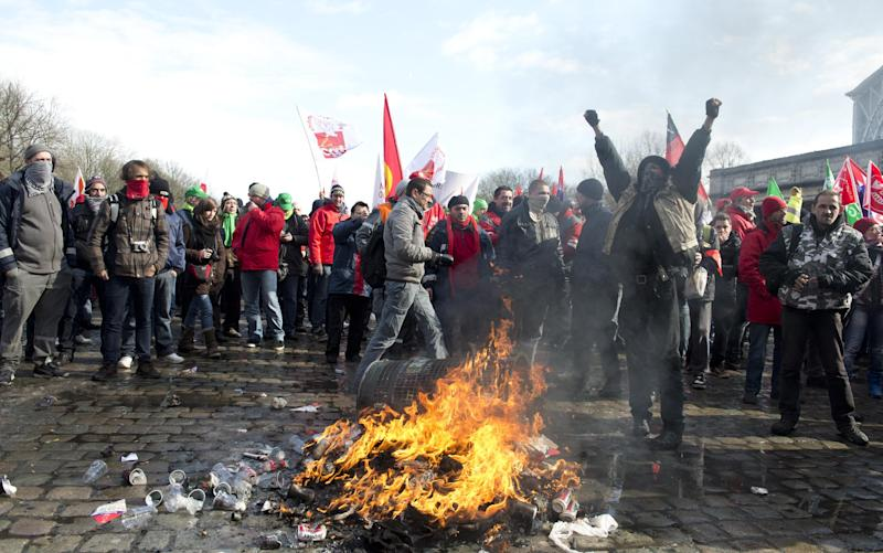 Union members light a fire during a demonstration outside of an EU summit in Brussels on Thursday, March 14, 2013. Thousands of workers are converging on EU headquarters to demand an end to austerity measures in a demonstration coinciding with an EU summit aimed at boosting growth and reducing unemployment. Thursday's protest showed frustration of the European trade union movement claiming years of austerity imposed by EU leaders is only worsening the recession while driving ever more people toward unemployment and poverty. (AP Photo/Geert Vanden Wijngaert)