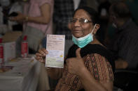 A beneficiary gestures after getting a COVISHIELD vaccine shot at a government hospital in Noida, a suburb of New Delhi, India, Monday, March 1, 2021. India is expanding its COVID-19 vaccination drive beyond health care and front-line workers, offering the shots to older people and those with medical conditions that put them at risk. As of Monday, those eligible to be vaccinated include people over 60, as well as those over 45 who have ailments such as heart disease or diabetes that make them vulnerable to the coronavirus. (AP Photo/Altaf Qadri)