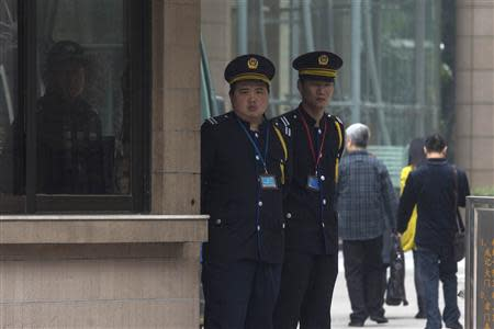 A police officer (L) and security officers stand guard outside the Southern Weekly newspaper office in the southern Chinese city of Guangzhou January 7, 2014. REUTERS/Tyrone Siu