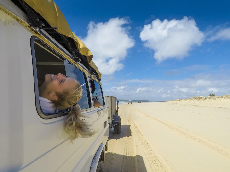 A girl sticks her head out the window as she drives down the beach.