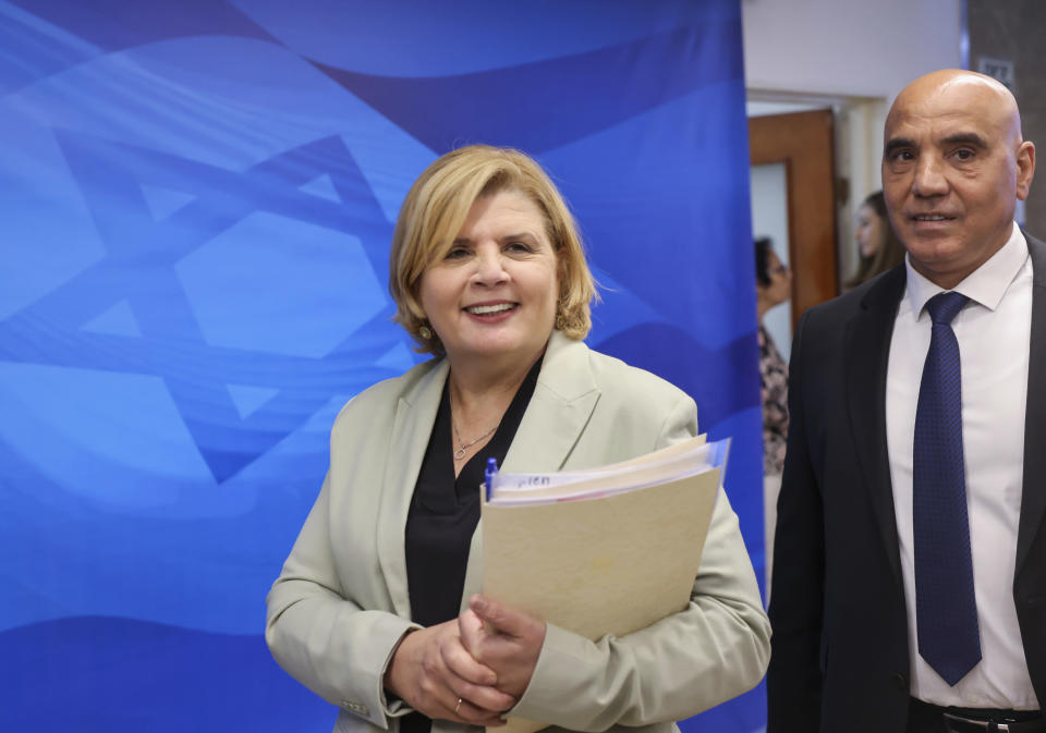 """Israeli Minister of Economy Orna Barbivai, left, and Minister in the Finance Ministry Hamad Amar arrive to attend the first weekly cabinet meeting of the new government in Jerusalem, Sunday, June 20, 2021. Prime Minister Naftali Bennett opened his first Cabinet meeting on Sunday since swearing in his new coalition government with a condemnation of the newly elected Iranian president, whom he called """"the hangman of Tehran."""" (Emmanuel Dunand/Pool Photo via AP)"""