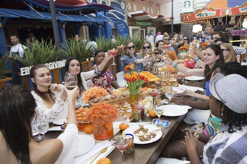 This Nov. 11, 2016 photo provided by Royal Caribbean International shows guests gathered for a Friendsgiving celebration at sea aboard the Royal Caribbean cruise ship Harmony of the Seas. Friendsgiving is a twist on Thanksgiving, usually a gathering of friends getting together on a day other than the traditional Thursday holiday. When hosted at home, it's often a potluck party, but this year Royal Caribbean offered an organized Friendsgiving at sea for passengers. (Simon Brooke-Webb/Royal Caribbean via AP)