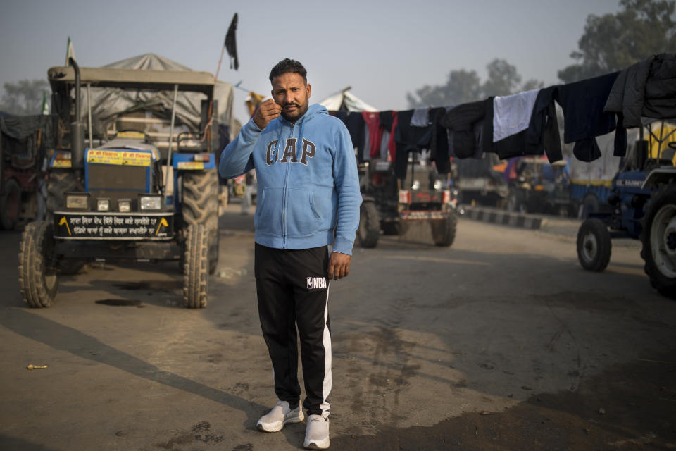 "Hardeep Singh, 42, stands for a photograph next to his tractor trailer parked on a highway as he joins tens of thousands of protesting farmers for a protest against new farm laws at the Delhi-Haryana state border, India, Tuesday, Dec. 1, 2020. The protests started in September but drew nationwide attention last week when the farmers marched from northern Punjab and Haryana, two of India's largest agricultural states. Their rallying call is ""Inquilab Zindabad"" (""Long live the revolution""). (AP Photo/Altaf Qadri)"
