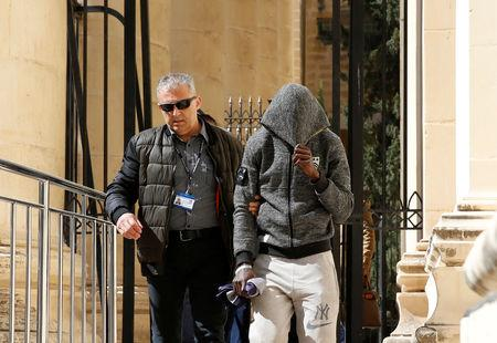 One of the migrants charged with hijacking the merchant ship Elhiblu 1 is escorted by a police officer out of the Courts of Justice in Valletta Malta