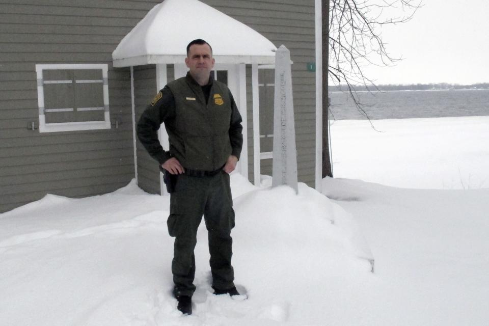 In this Monday Feb. 10, 2020, photo, U.S. Border Patrol Agent Dustin Judd poses near a border marker in Alburgh, Vt. Statistics show that the 295-mile Swanton Sector of upstate New York, Vermont and New Hampshire, sees the most illegal border crossing of any sector along the 4,000-mile U.S.-Canadian border. (AP Photo/Wilson Ring)
