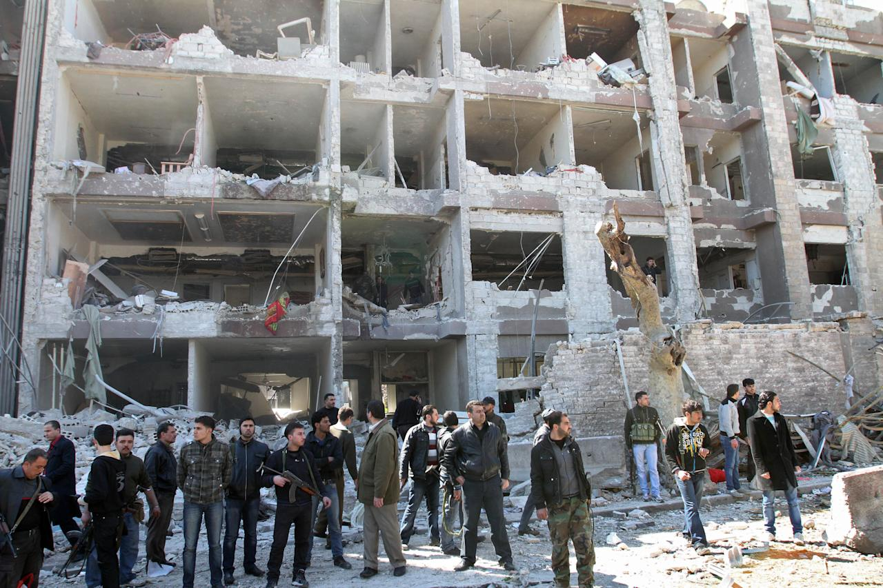 Syrian security officers gather in front the damaged building of the aviation intelligence department, which was attacked by one of two explosions, in Damascus, Syria, on Saturday, March 17, 2012. Twin bombings struck government targets in the Syrian capital early Saturday, killing security forces and civilians and leaving pools of blood and carnage in the streets, according to state-run television. (AP Photo/Bassem Tellawi)