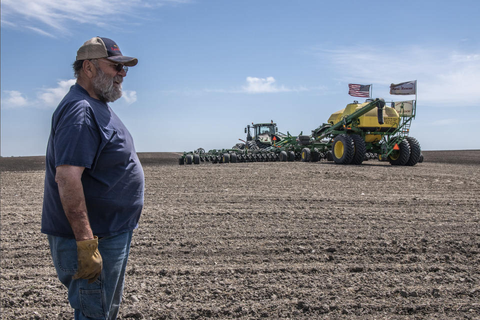 In this photo provided by Farm Rescue, volunteer Emil Baranko watchers as other volunteers plant crops on Paul Ivesdal's farm June 3, 2020 in Edmore, N.D. The wet spring offered only a tiny window for planting, so when Ivesdal fell ill to a coronavirus infection he knew the timing couldn't be worse. Thanks to Farm Rescue, Ivesdal got his crop in even as he was rushed to a hospital and spend eight days on a ventilator. The nonprofit organization's help meant that although Ivesdal spent a summer in rehabilitation to recover his walking ability and even now tires more easily, he'll be able to keep farming. (Dan Erdmann/Farm Rescue via AP)