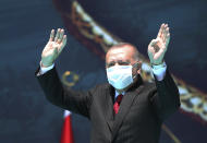Turkey's President Recep Erdogan waves as he attends celebrations marking the anniversary of the 1071 battle of Manzikert, during which Turkish Seljuks beat Byzantine forces, gaining entry into Anatolia, in Malazgirt, eastern Turkey, Wednesday, Aug. 26, 2020. Erdogan warned Greece on Wednesday not to test his country's patience or courage, further stoking tensions between the NATO allies over offshore energy exploration in the eastern Mediterranean.(Turkish Presidency via AP, Pool)