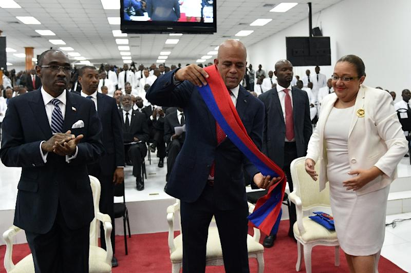 Haitian President Michel Martelly (C) takes off his presidential sash during a ceremony in parliament in Port-au-Prince on February 7, 2016 (AFP Photo/Hector Retamal)