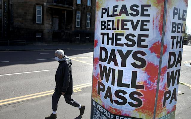 A person walks passed a billboard poster outside Glasgow Royal Infirmary as the UK continues in lockdown. (PA)