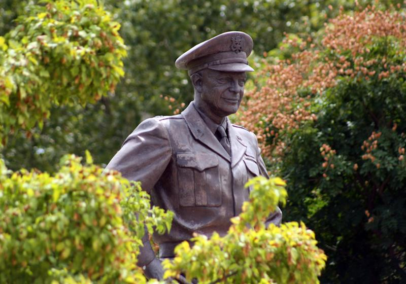 This Aug. 4, 2012 photo shows a large bronze statue of Gen. Eisenhower that stands over the grounds of his library, museum and boyhood home in Abilene, Kansas. The museum plans to launch a new World War II exhibit begging in the summer of 2013. A new World War II exhibit starting this summer at the Eisenhower Presidential Library and Museum will pay tribute to the millions who fought, but organizers also have another purpose for the ambitious three-year project: getting young people engaged in the war's relevance.(AP Photo/John Milburn)