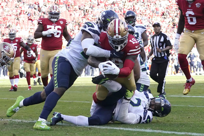 San Francisco 49ers wide receiver Deebo Samuel, middle, scores a touchdown against Seattle Seahawks linebacker Jordyn Brooks, top, and cornerback D.J. Reed during the second half of an NFL football game in Santa Clara, Calif., Sunday, Oct. 3, 2021. (AP Photo/Tony Avelar)