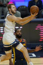Minnesota Timberwolves forward Jake Layman, top, shoots over Golden State Warriors guard Brad Wanamaker during the first half of an NBA basketball game in San Francisco, Monday, Jan. 25, 2021. (AP Photo/Jeff Chiu)