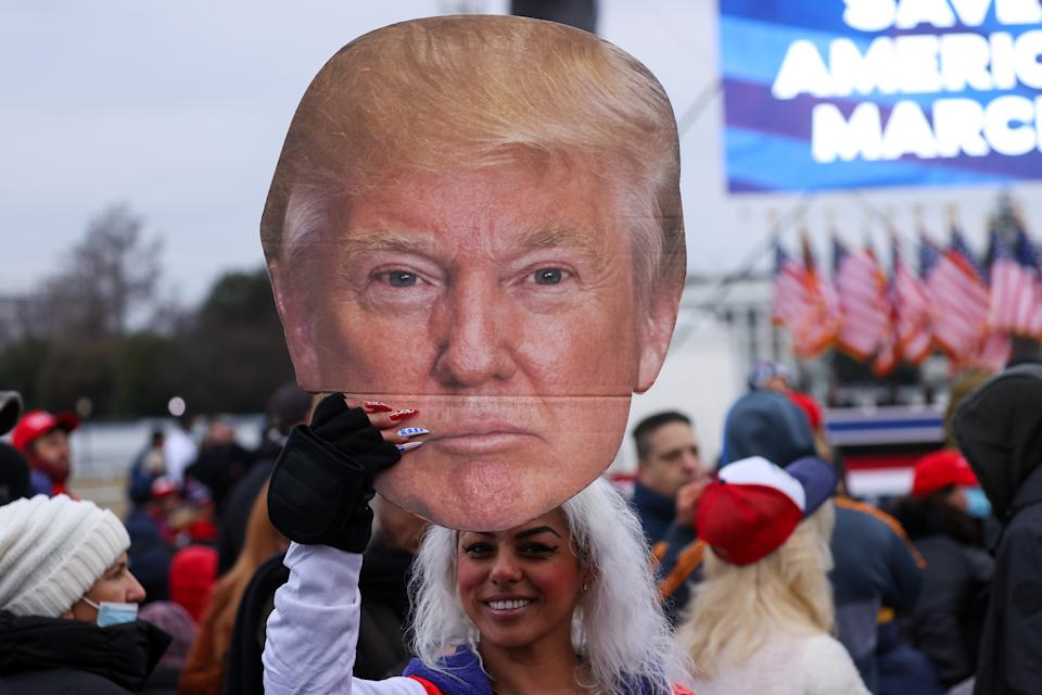 """WASHINGTON, USA - JANUARY 06: A supporter holds a US President Donald Trump cardboard during a """"Save America Rally"""" near the White House in Washington, D.C., U.S., on Wednesday, Jan. 6, 2021. The House and Senate will meet in a joint session today to count the Electoral College votes to confirm President-elect Joe Biden's victory, but not before a sizable group of Republican lawmakers object to the counting of several states' electors. (Photo by Tayfun Coskun/Anadolu Agency via Getty Images)"""