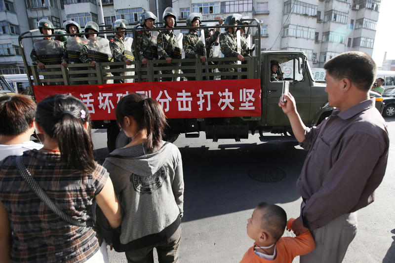 "FILE - In this file photo taken Thursday, July 9, 2009, bystanders look at a truckload of paramilitary police with a banner which reads ""Determined crackdown on separatist activities"" patrol in the aftermath of riots in Urumqi in western China's Xinjiang province, Analysts say the Urumqi riots in 2009 set in motion the harsh security measures now in place across Xinjiang, where about 1 million Uighurs, Kazakhs and other Muslims are estimated to be held in heavily-guarded internment camps _ also called ""re-education"" camps _ which the Chinese government describes as vocational training centers. (AP Photo/Eugene Hoshiko, File)"