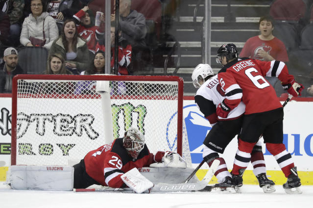 New Jersey Devils goaltender MacKenzie Blackwood (29) makes a save against Arizona Coyotes center Clayton Keller, center, during overtime of an NHL hockey game, Saturday, March 23, 2019, in Newark, N.J. Devils' Andy Greene helps defend on the play. The Devils on 2-1 in a shootout. (AP Photo/Julio Cortez)