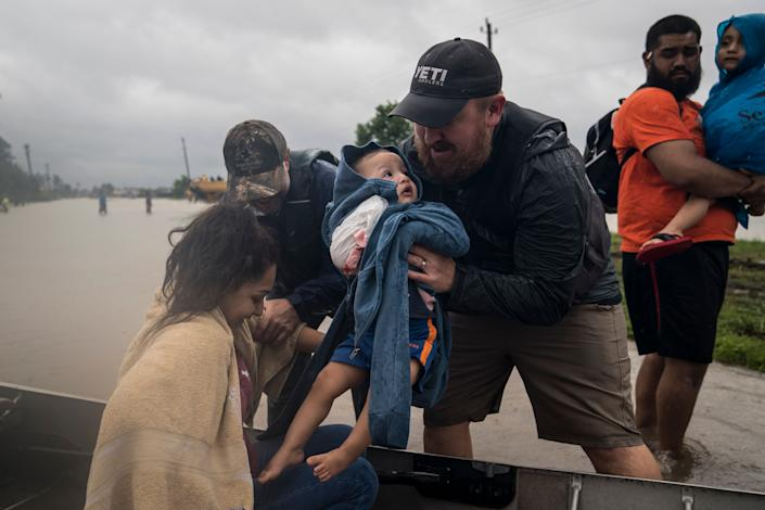 Glenda Montelongeo, Richard Martinez and his two sons are helped out of a boat after being rescued near Tidwell Road and Toll road 8 in Houston.
