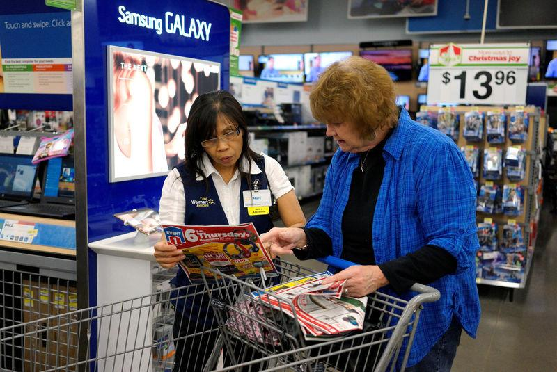 FILE PHOTO: A Walmart employee helps a customer navigate a sale flyer at the store in Broomfield
