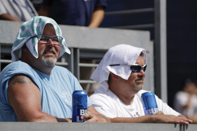 Fans cover their heads to protect against the sun during the seventh inning of a baseball game between the New York Yankees and the Colorado Rockies at Yankee Stadium Saturday, July 20, 2019, in New York. (AP Photo/Frank Franklin II)