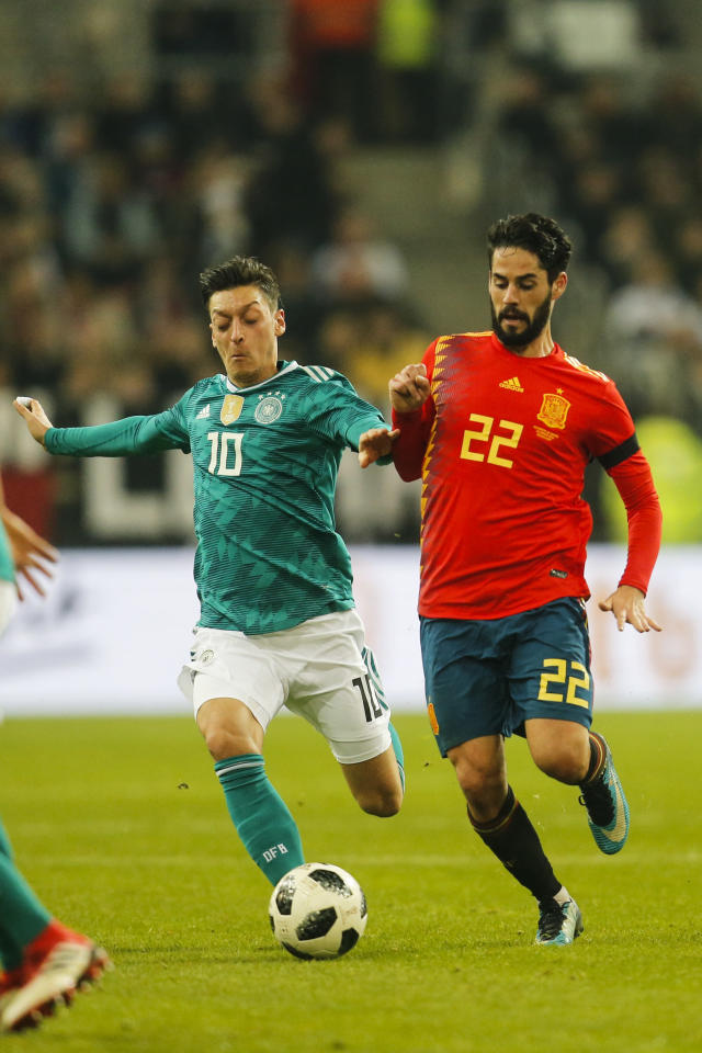 Germany's Mesut Ozil, left, and Spain's Isco Alarcon, right, challenge for the ball during an international friendly soccer match between Germany and Spain in Duesseldorf, Germany, Friday, March 23, 2018. (AP Photo/Michael Probst)