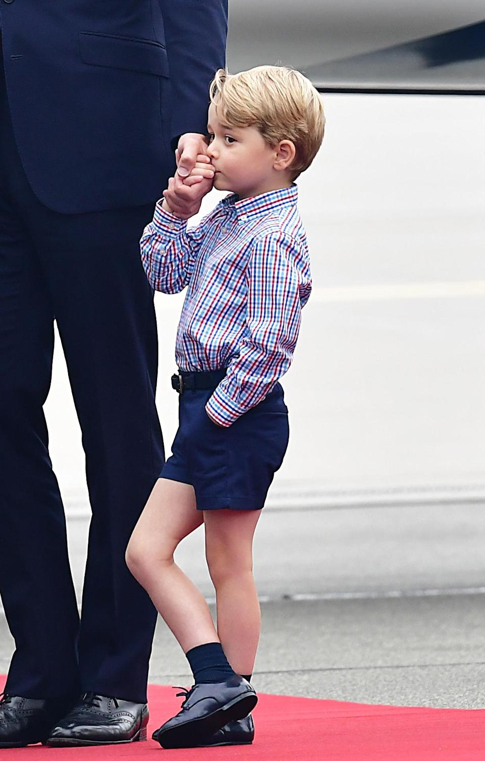 <p><b><b><b>Prince George, dressed in a checked shirt and tailored shorts, appeared rather shy in front of the arrival committee and press at Warsaw's Chopin Airport. <em>[Photo: PA]</em> </b></b></b></p>