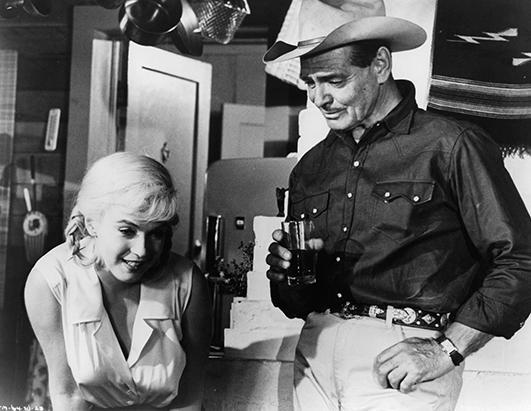Marilyn Monroe sitting as Clark Gable stands over her with a glass in his hand in a scene from the film 'The Misfits', 1961