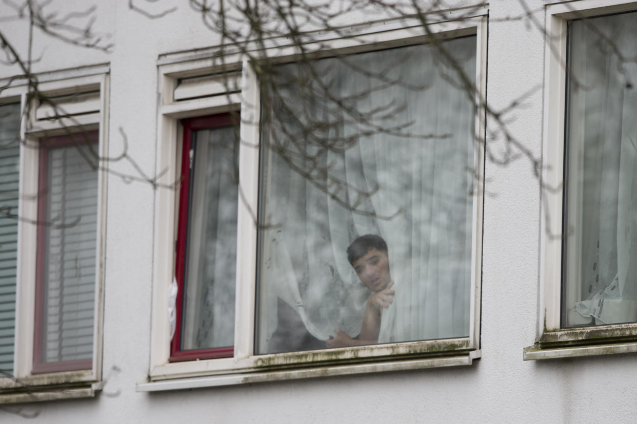 A resident peers out from a window as Dutch counter terrorism police prepare to enter a house after a shooting incident in Utrecht, Netherlands, Monday, March 18, 2019. (Photo: Peter Dejong/AP)