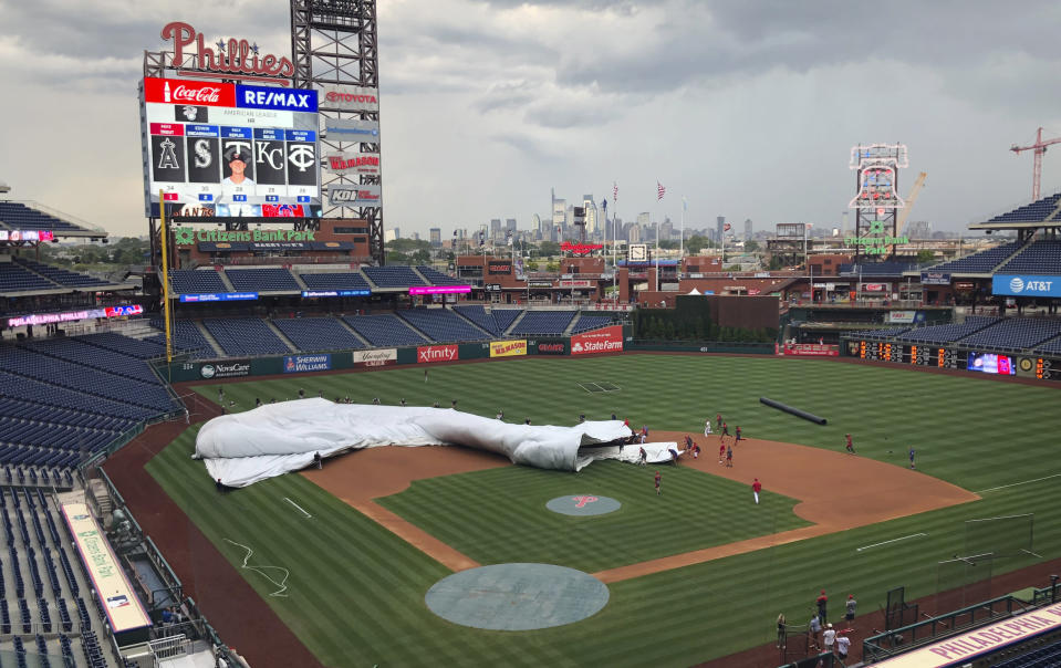 Members of the San Francisco Giants and Philadelphia Phillies join the grounds crew at Citizens Bank Park to help put the tarp on the field several hours before a scheduled baseball game in Philadelphia on Wednesday, July 31, 2019. A sudden burst of wind sent the tarp flapping, and players rushed in to help weigh it down. (AP Photo/Rob Maaddi)