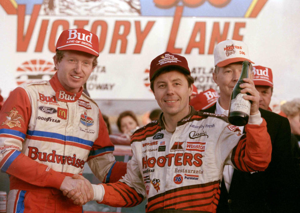 FILE - Hooters 500 winner Bill Elliott, left, and NASCAR Winston Cup champion Alan Kulwicki celebrate in Victory Lane following the Hooters 500 at Atlanta Motor Speedway in Hampton, Ga., in this Nov. 15, 1992, file photo. Chase Elliott will honor the late Alan Kulwicki by racing the same Hooters paint scheme that was on Kulwicki's car in the 1992 season finale at Atlanta Motor Speedway when Kulwicki beat Bill Elliott for the Winston Cup title. Chase Elliott will run the paint scheme at Darlington Raceway on May 9, 2021. (AP Photo/John Bazemore, File)