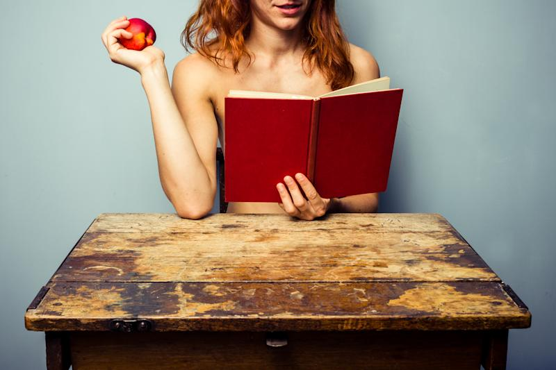 Naked woman is sitting at an old vintage school desk and reading a red book while holding a peach.