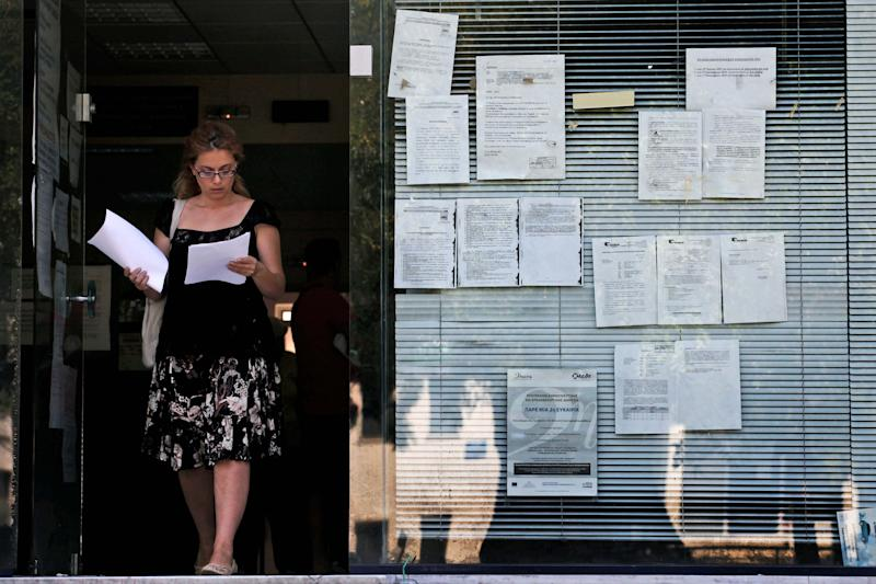 A woman leaves an unemployment bureau in Athens on Thursday, Sept. 6, 2012. Greece's unemployment rate surged to 24.4 percent in June as the number of people out of work in June rose by 34,000 to more than 1.2 million. (AP Photo/Petros Giannakouris)