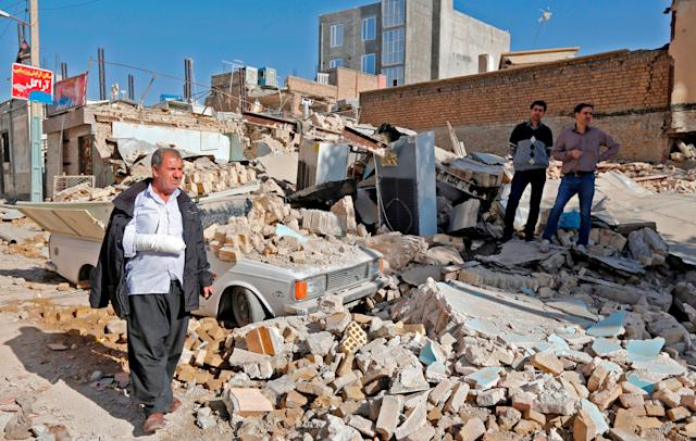 An injured Iranian walks through rubble in Sarpol-e Zahab, a town in Iran's western Kermanshah Province, on Tuesday.