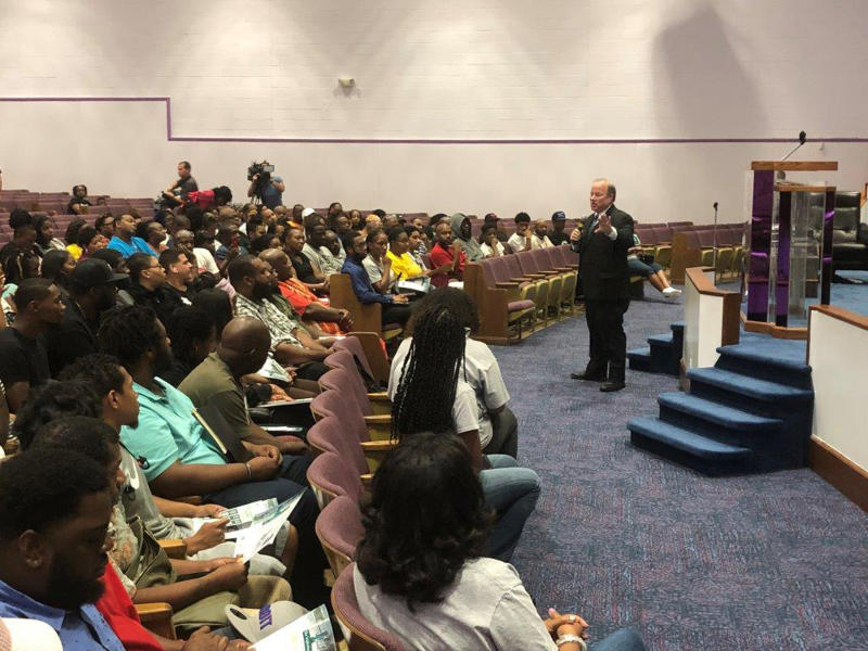 In this Aug. 6, 2019 photo, Detroit Mayor Mike Duggan speaks with Detroit residents during a job readiness event where they pre-registered to apply for jobs at a coming Fiat Chrysler assembly plant on the eastside and another nearby facility operated by the automaker. Fiat Chrysler is giving Detroit residents an exclusive 30-day window to apply for about 4,900 mostly production jobs as part of a $108 million land development deal with the city. (AP Photo/Corey Williams)