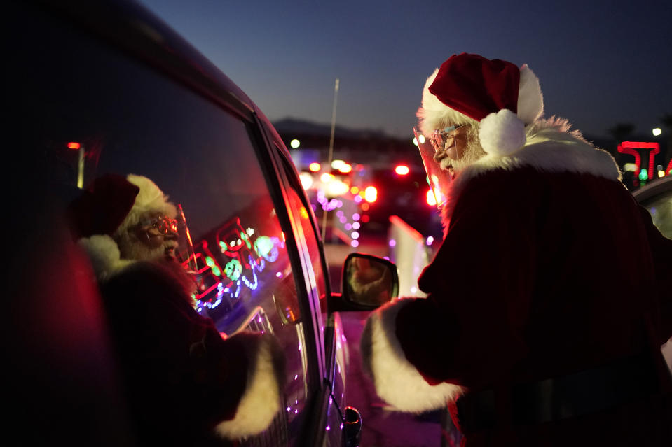 Charlie Bush, dressed as Santa Claus, wears a face shield as a precaution against coronavirus as he greets people waiting in their cars at Glittering Lights, a drive-thru holiday lights display, Thursday, Dec. 10, 2020, in Las Vegas. In this socially distant holiday season, Santa Claus is still coming to towns (and shopping malls) across America but with a few 2020 rules in effect. (AP Photo/John Locher)