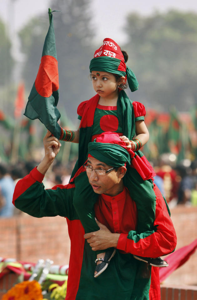 A young Bangladeshi child holds a national flag as she is carried by her father on his shoulders outside the National Memorial during the Independence Day celebrations at Saver on the outskirts of Dhaka, Bangladesh, Monday, March 26, 2012. Bangladesh celebrates its 41st independence day Monday. (AP Photo/Pavel Rahman)